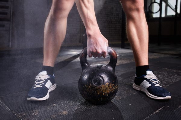 Closeup photo of young man's legs in sneackers and arm while keeping kettlebell against dark background. Crossfit workout. Detail of crossfit man. Healthy lifestyle.